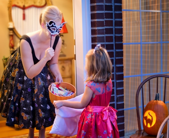 Woman giving trick-o-treater candy
